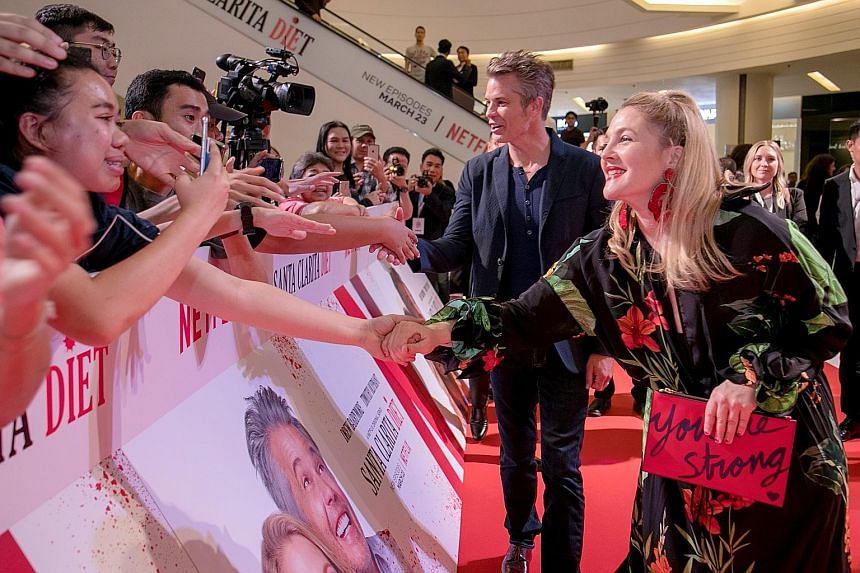 Actors Timothy Olyphant and Drew Barrymore greeting fans at an event in Bangkok yesterday to promote the second season of Santa Clarita Diet.