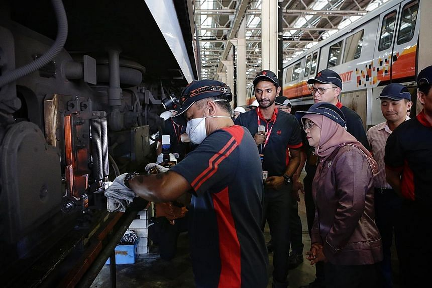 President Halimah Yacob observing maintenance work being done on the undercarriage of a train during her visit to SMRT's Bishan Depot yesterday.