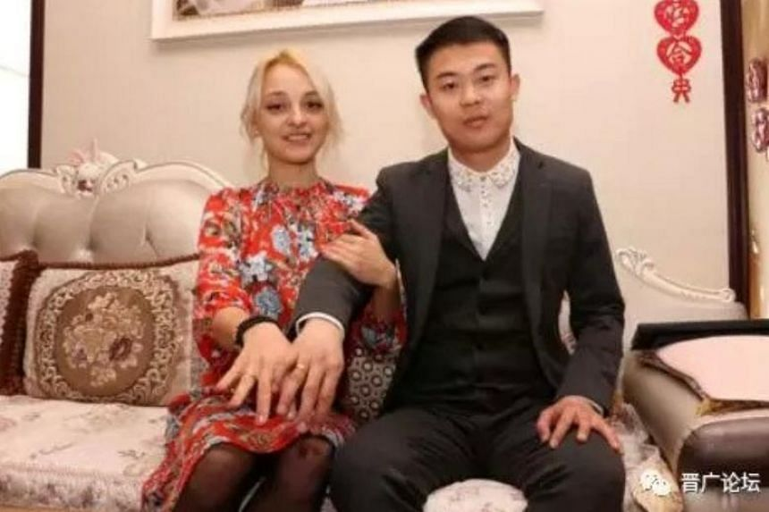 """Mr He Pengwei, from Yangcheng county in the northwestern Shanxi province with his bride, Ms Inesa, who did not want a """"bride price""""."""