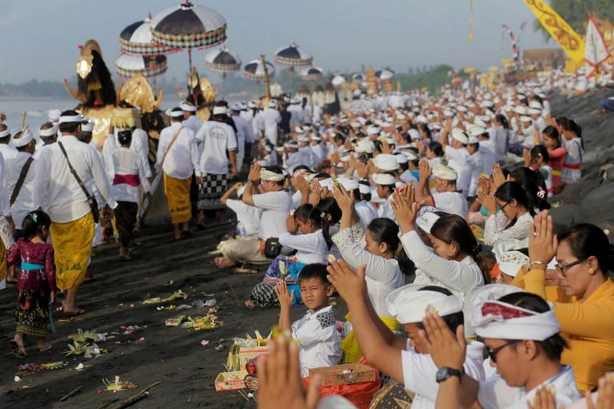 Balinese Hindus pray along a beach during a Melasti purification ceremony ahead of the holy day of Nyepi in Gianyar, Bali, Indonesia, on March 14, 2018.