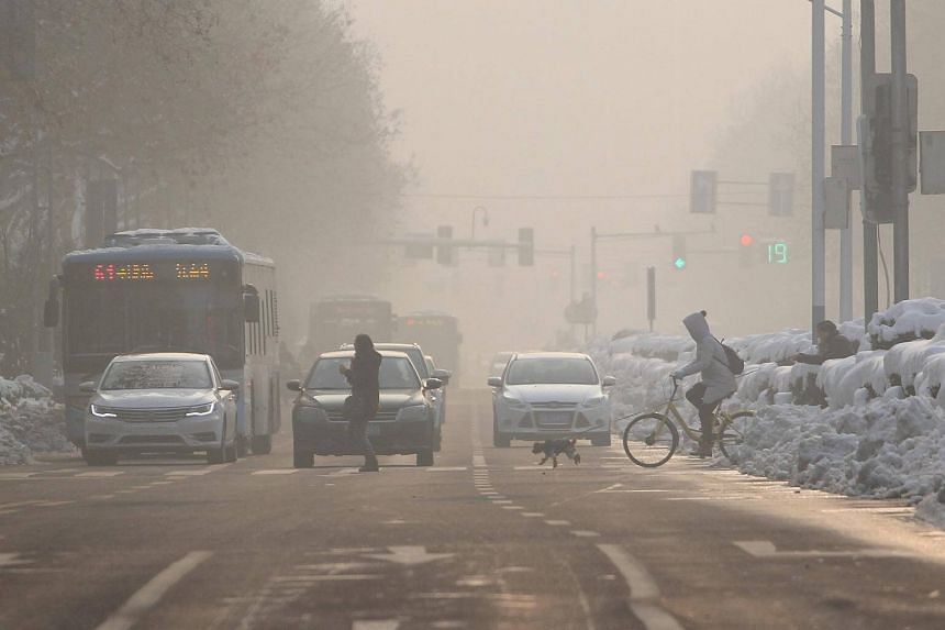 Pedestrians cross a road amidst smog on a polluted day in Nanjing, Jiangsu province, China, on Jan 30, 2018.
