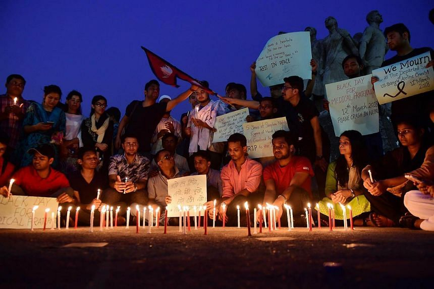 Nepali students, who study in Bangladesh, take part in a candlelight vigil in honour of the Kathmandu plane crash victims in Dhaka, on March 13, 2018.