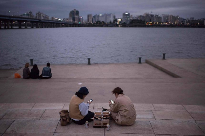 Women looking at their phones as they sit before the Han river and city skyline in Seoul, Korea.