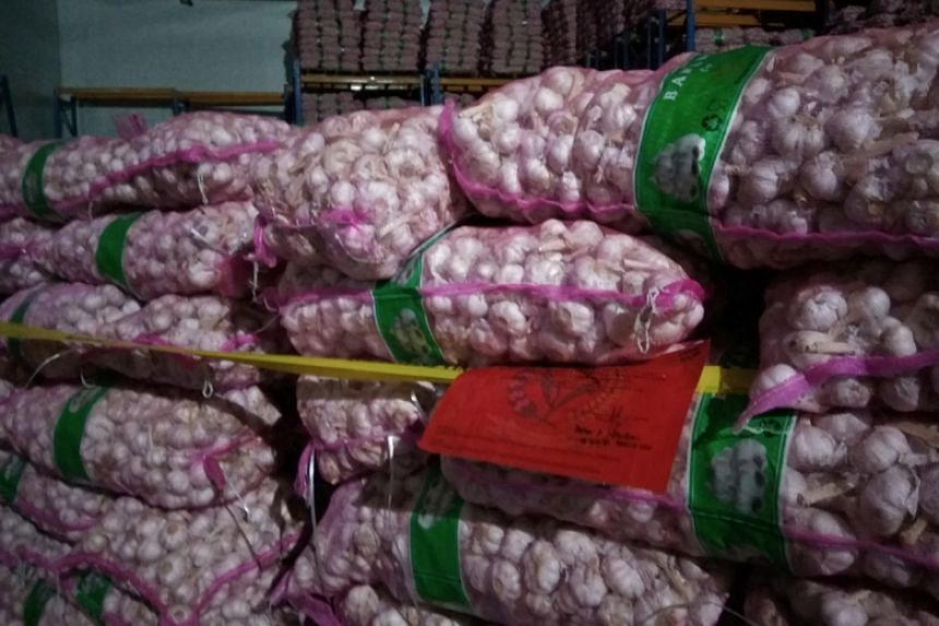 Police tape is seen around confiscated garlic from China at a warehouse in Belawan, Indonesia, on March 13, 2018.