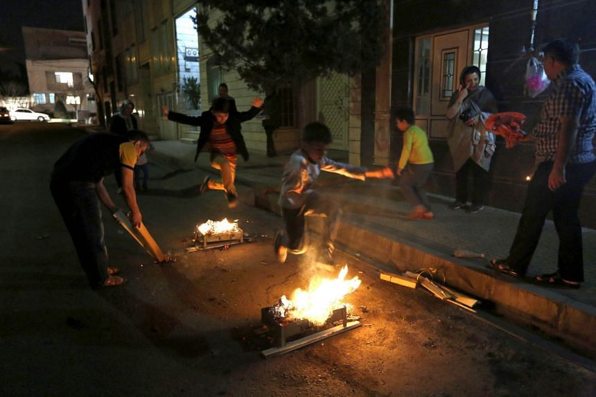 Iranians light fire outside their hones in Teheran during the Wednesday Fire feast, or Chaharshanbeh Soori.