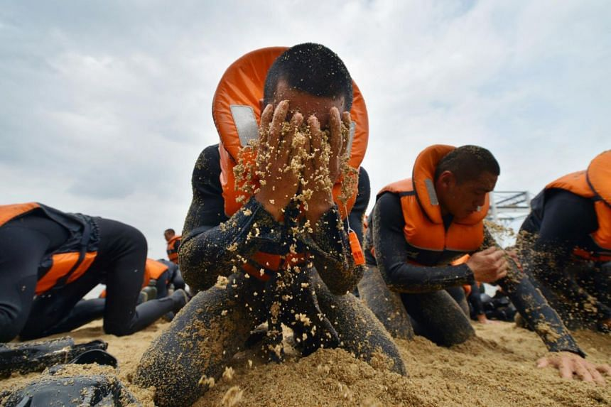 A trainee rubbing sand into his face during a Wet and Sandy session on the beach, where trainees are made to cover every inch of their bodies with sand during the five-month Combat Diver Course.