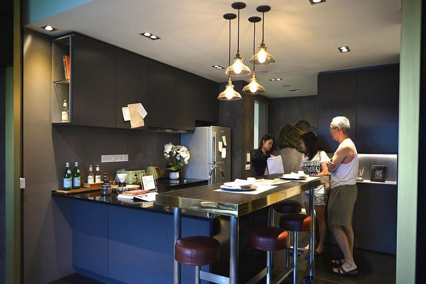 Potential buyers view a one-bedroom showflat unit at a showroom.
