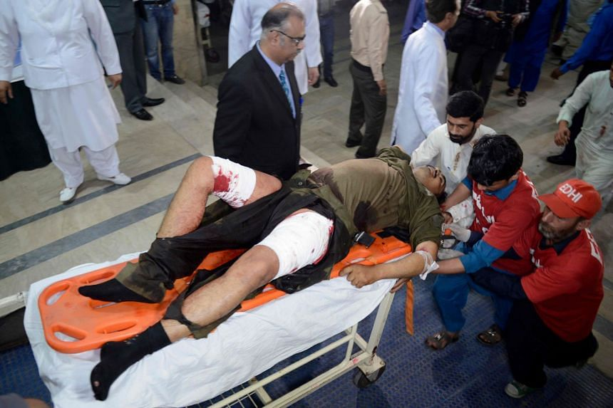 Pakistani volunteers push a stretcher carrying an injured blast victim to the hospital.