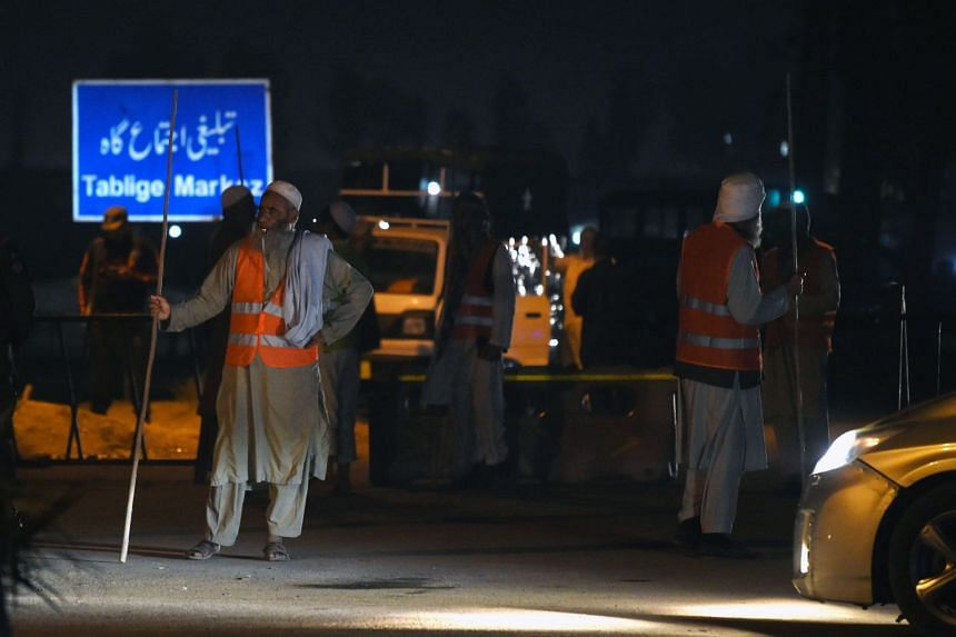 Pakistani Islamic religuous volunteers stand guard near the site of a motorcycle bomb attack in Lahore.