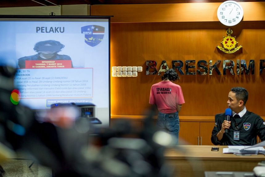 Indonesian cyber crime police displaying a suspect accused of spreading fake news and online hate speech in Jakarta on March 8, 2018.
