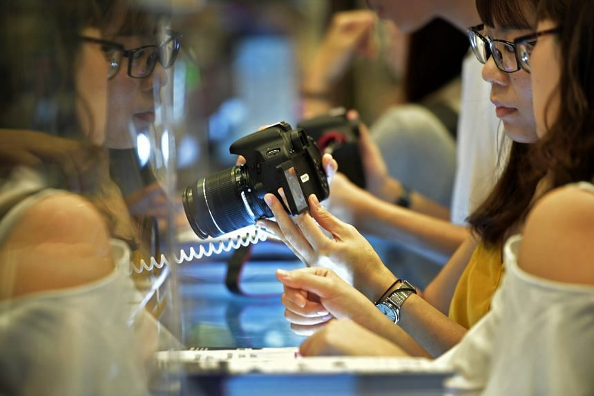 Visitors look at cameras at the Sony booth of the IT Show 2018 held at the Suntec Singapore Convention and Exhibition Centre on March 15, 2018.