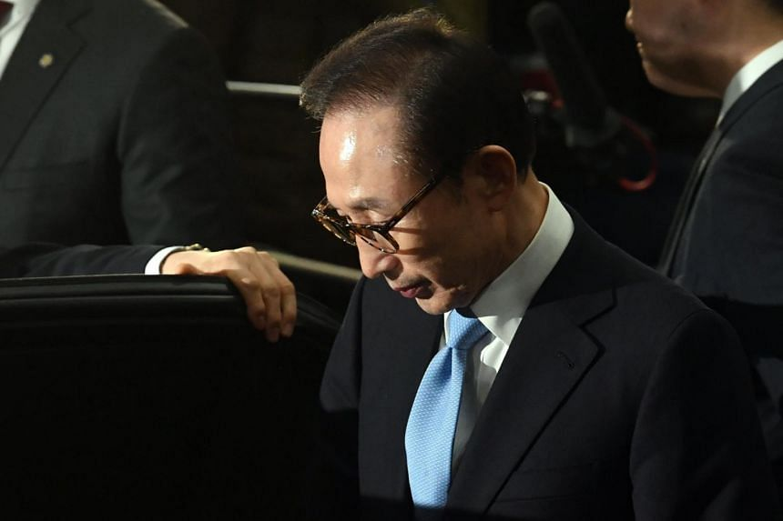 Former South Korean President Lee Myung Bak leaves the Seoul Central District Prosecutors' Office on March 15, 2018, after more than 21 hours of questioning over multiple corruption allegations.