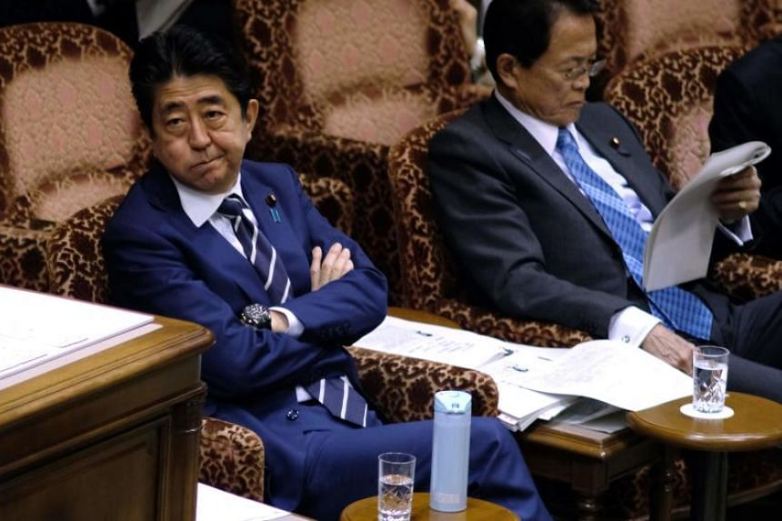 Japan's Prime Minister Shinzo Abe and Finance Minister Taro Aso (right) attend an upper house budget committee session of parliament in Tokyo on March 8, 2018.