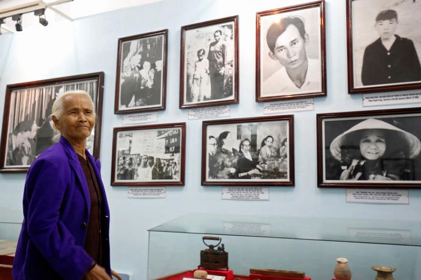 My Lai massacre survivor Pham Thi Thuan stands in front of photographs of her and other survivors exhibited at a museum during the 50th anniversary of the massacre in My Lai village, Vietnam on March 15, 2018.