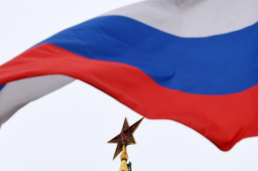 A Russian flag flies in front of a ruby star atop one of the Kremlin's towers in downtown Moscow on March 13, 2018.