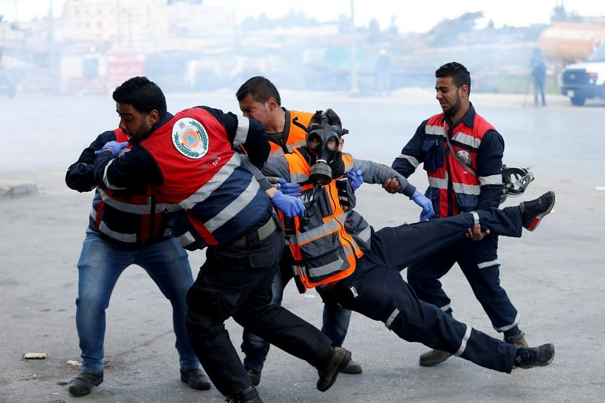 An injured Palestinian medic is evacuated during clashes between Palestinians and Israeli troops in the occupied West Bank.
