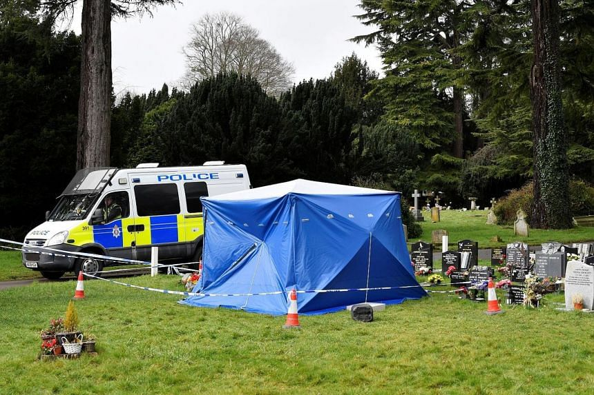 A police van and a tent covering the headstone of Alexander Skripal, the son of former Russian double agent Sergei Skripal, in Salisbury in Britain yesterday. The former spy and his daughter Yulia were found unconscious on a bench in the city on Marc