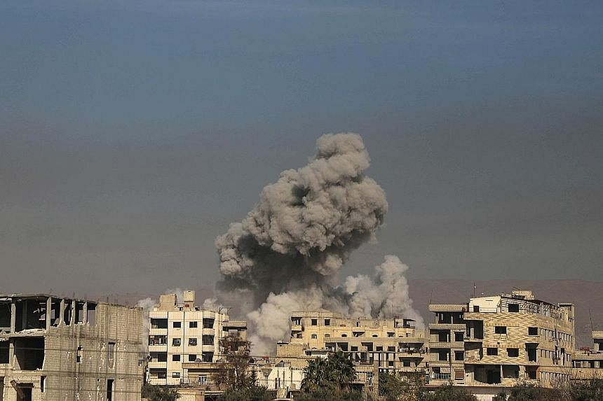 Smoke billowing in Hazeh in the beleaguered rebel enclave of Eastern Ghouta on the outskirts of Damascus yesterday. The Syrian Observatory for Human Rights said the town of Hammuriyeh in the enclave fell to regime forces after Islamist rebels from Fa