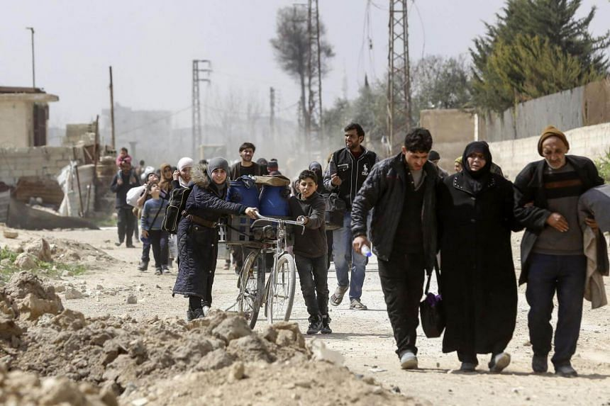 Syrians civilians evacuated from the Eastern Ghouta, pass with belongings through the regime-controlled corridor opened by government forces in Hawsh al-Ashaari, on the outskirts of the capital Damascus on March 15, 2018.