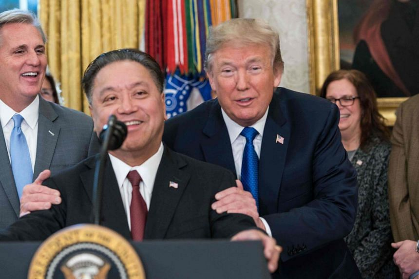 US President Donald Trump jokes with Broadcom CEO Tan Hock Eng in the Oval Office at the White House in Washington, DC on Nov 2, 2017.