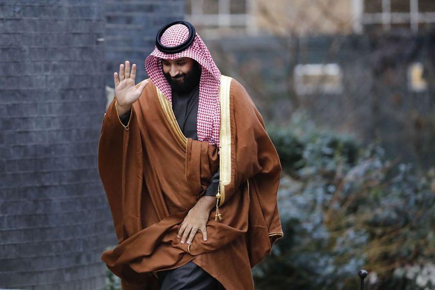 Crown Prince Mohammed bin Salman waves as he arrives for talks in London.