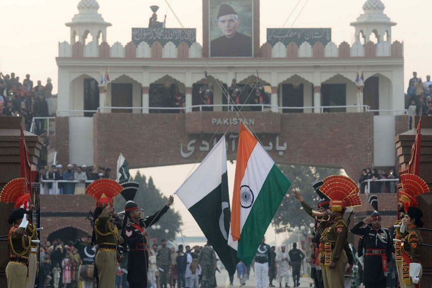 Pakistani Rangers (black uniforms) and Indian Border Security Force personnel (brown uniforms) take part in the daily beating of the retreat ceremony at the India-Pakistan Wagah Border Post, on Dec 24, 2017.