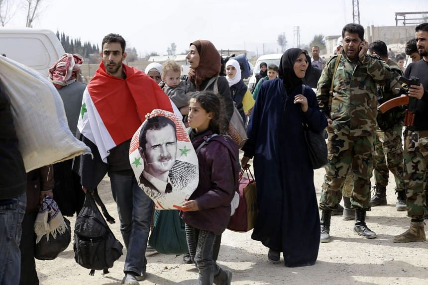 A Syrian man draped in the national flag walks with a girl carrying a poster of President Bashar al-Assad, as they pass with other civilians evacuated from Eastern Ghouta.