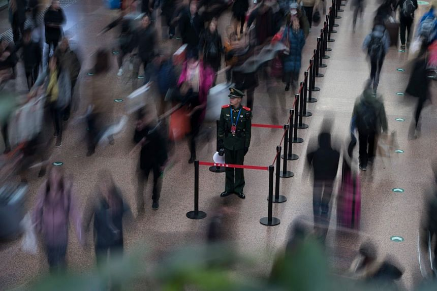 A Chinese soldier standing in the main hall while travellers rush before boarding trains at the West Railway Station in Beijing on Feb 10, 2018.
