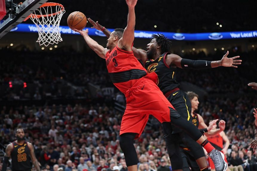 Portland Trail Blazers guard CJ McCollum shoots over Cleveland Cavaliers guard John Holland in the second half of their NBA game at Moda Center in Portland on March 15, 2018.