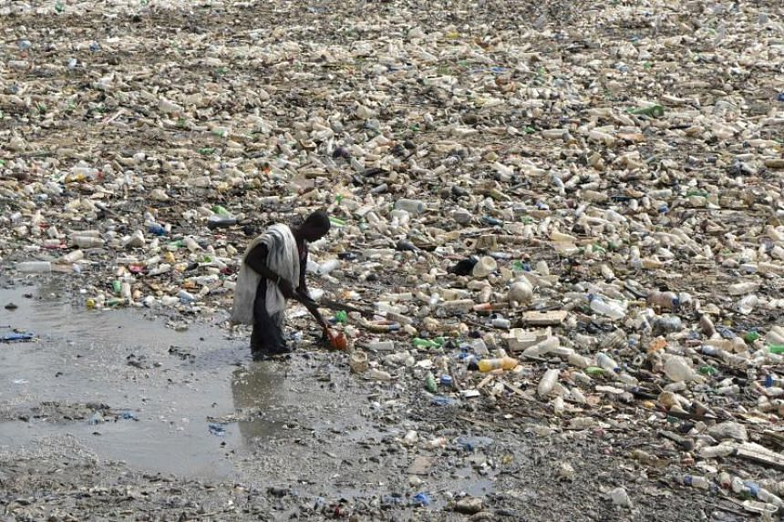 A man collects plastic from a waste water evacuation canal in the Ebrie Lagoon in Abidjan, on Feb 19, 2018.