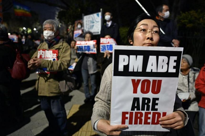 Protesters hold placards against Japanese Prime Minister Shinzo Abe during a rally before the National Diet in Tokyo on March 15, 2018.