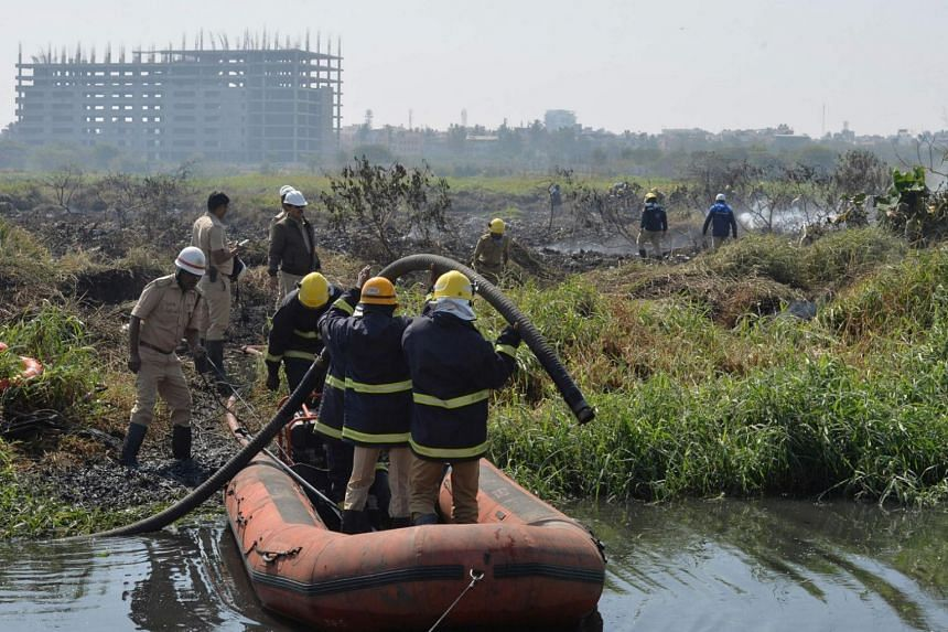 Firefighters work next to a doused fire on the polluted Bellandur Lake that is clogged with vegetation in Bangalore, India, on Jan 20, 2018.