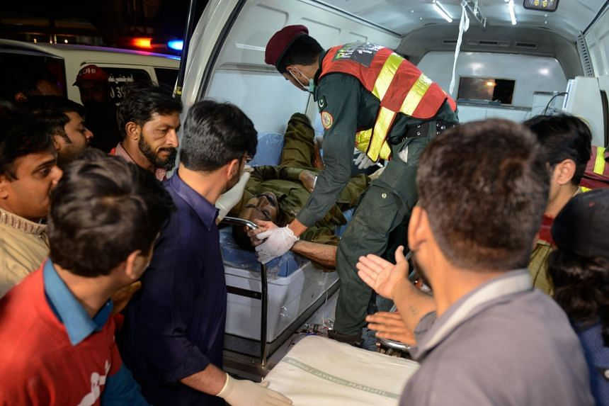 Rescue workers shift an injured policeman from the scene of a suicide bomb blast near Lahore.