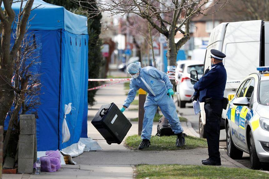Forensics investigators work at the home of Nikolai Glushkov in New Malden, on the outskirts of London.