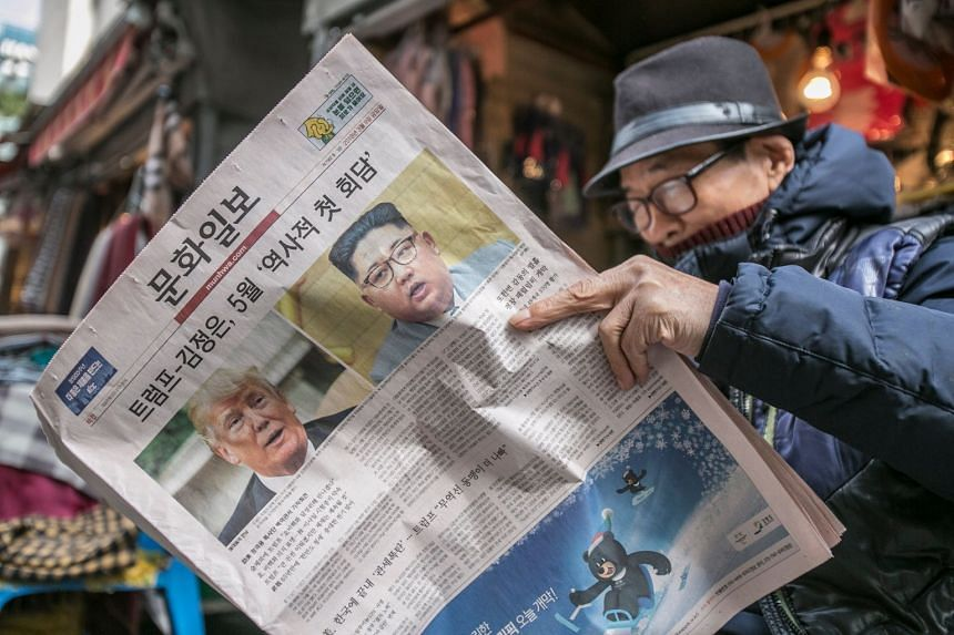 A man reads a newspaper featuring Trump and Kim on the front page in Seoul, South Korea.