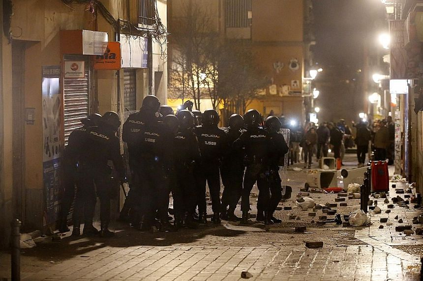 Spanish riot police facing off against protesters during a violent demonstration in Madrid on Thursday night. The protesters were angry over the death of a Senegalese street vendor who they said was chased through the streets by police. They set fire