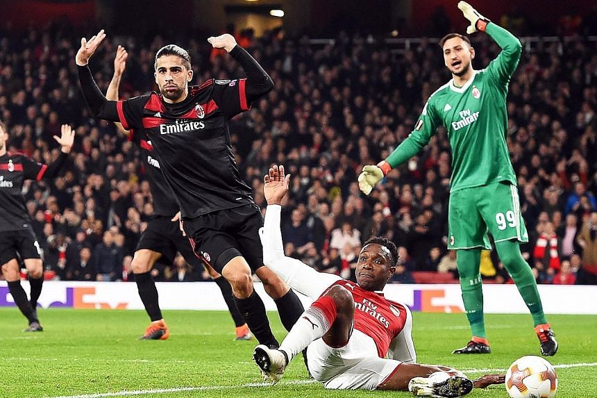 Arsenal forward Danny Welbeck going down in the box after AC Milan defender Ricardo Rodriguez's soft challenge in the box. The Switzerland international protested his innocence to little avail as the referee blew for a spot-kick, which Welbeck duly c