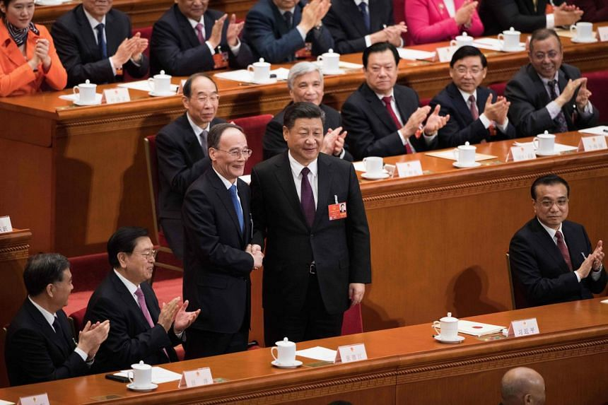 Newly-elected Vice-President Wang Qishan (centre) shakes hands with President Xi Jinping at the Great Hall of the People in Beijing on March 17, 2018.