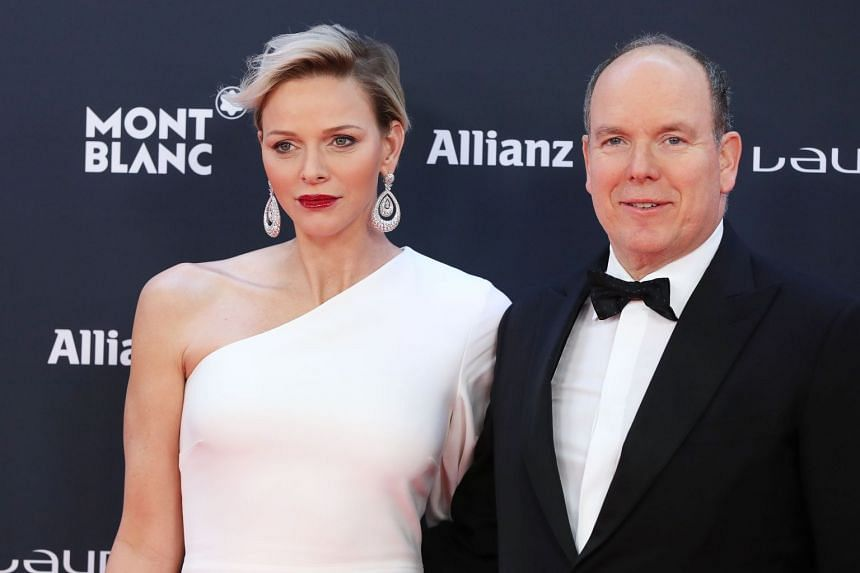 The real Prince Albert and Princess Charlene of Monaco pose at a red carpet event in February 2018.
