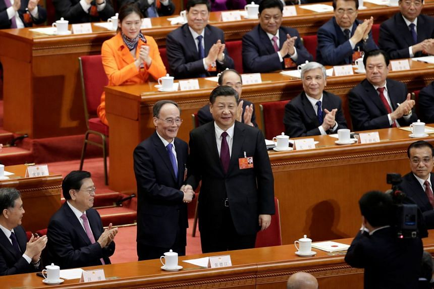 Chinese President Xi Jinping (centre, right) shakes hands with newly elected Chinese Vice-President Wang Qishan at the fifth plenary session of the National People's Congress (NPC), on March 17, 2018.