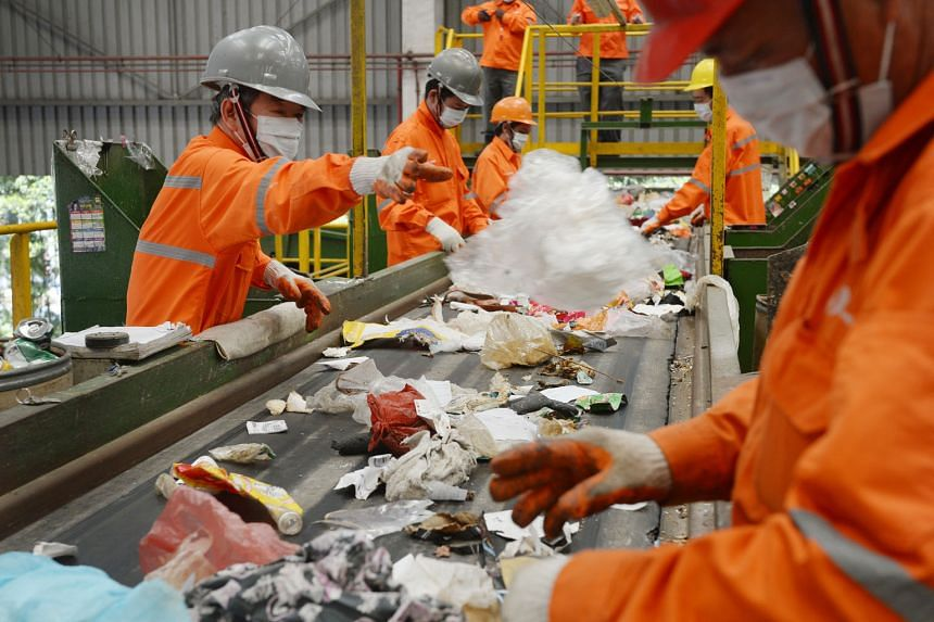 Staff at a SembWaste facility in Tuas picking out recyclable objects from trash. Recycling carries costs that are often overlooked, says the writer. For example, recycling paper could cause more severe water pollution or soil contamination as the rem