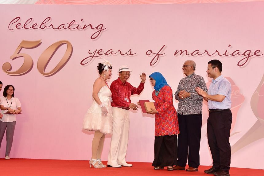 Madam Tay Mui Eng and Mr Bian Sin Teck, who have been married for 52 years, with President Halimah Yacob,  Mr Mohammed Abdullah Alhabshee and Minister for Social and Family Development Desmond Lee.