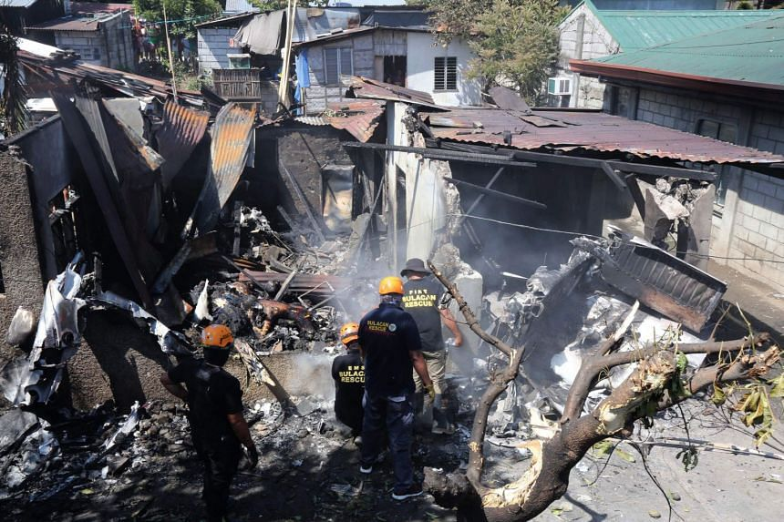 Rescue workers look at the site where they aircraft crashed in Plaridel, Bulacan, Philippines, on March 17, 2018.