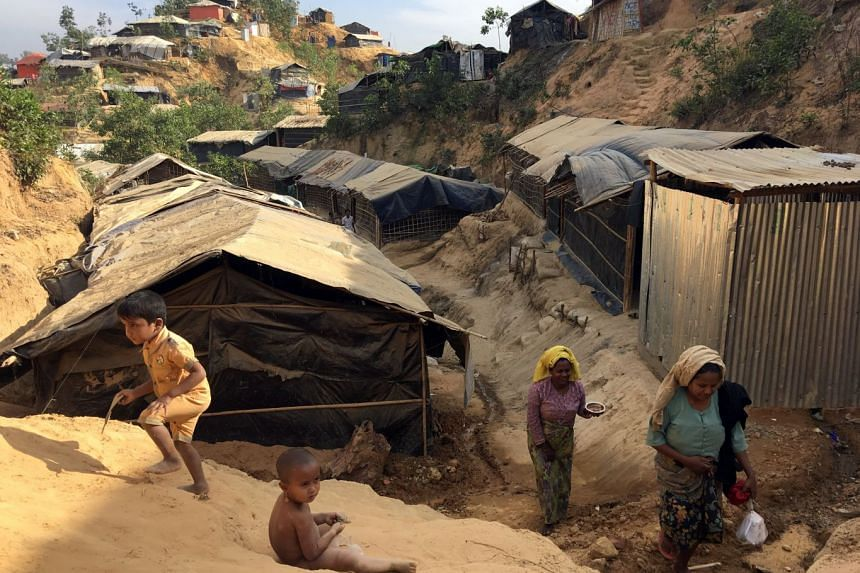 Women carry water jugs up a landslide-prone hill in the Balukhali camp for Rohingya refugees in southern Bangladesh, on Feb 13, 2018.