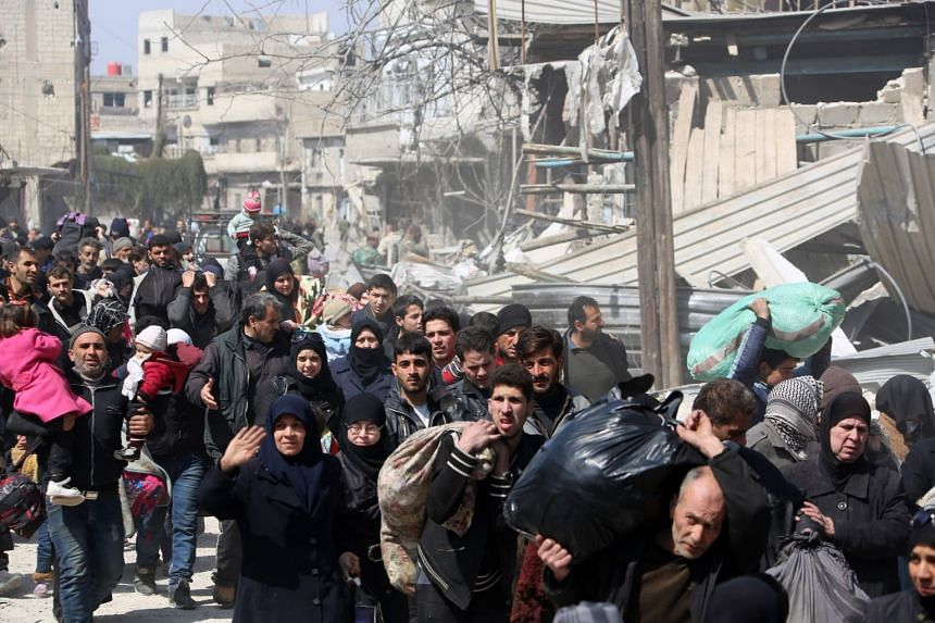 Syrian civilians evacuate from the town of Jisreen in the southern Eastern Ghouta, on the eastern outskirts of the capital Damascus, on their way to areas under government control, on March 17, 2018.