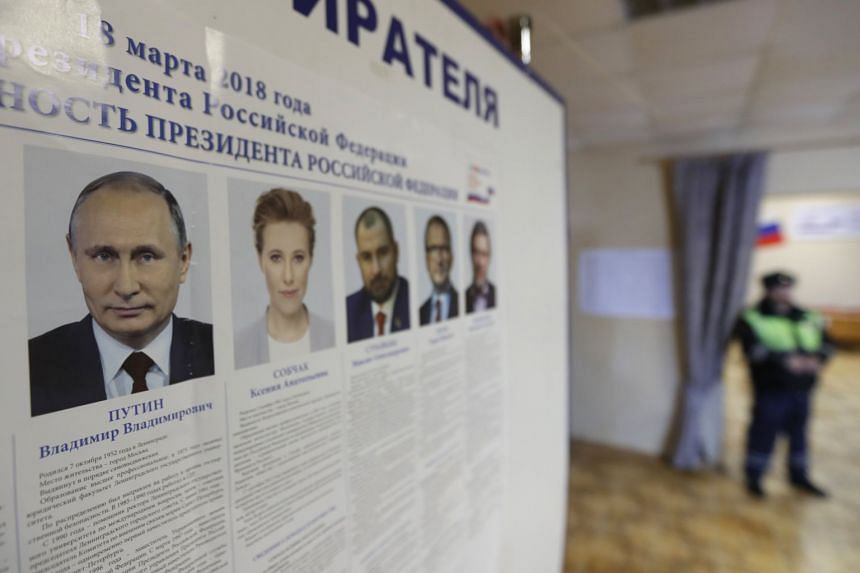 Pictures of presidential candidates are seen at a polling station in Borovsk some 10 km outside Moscow.