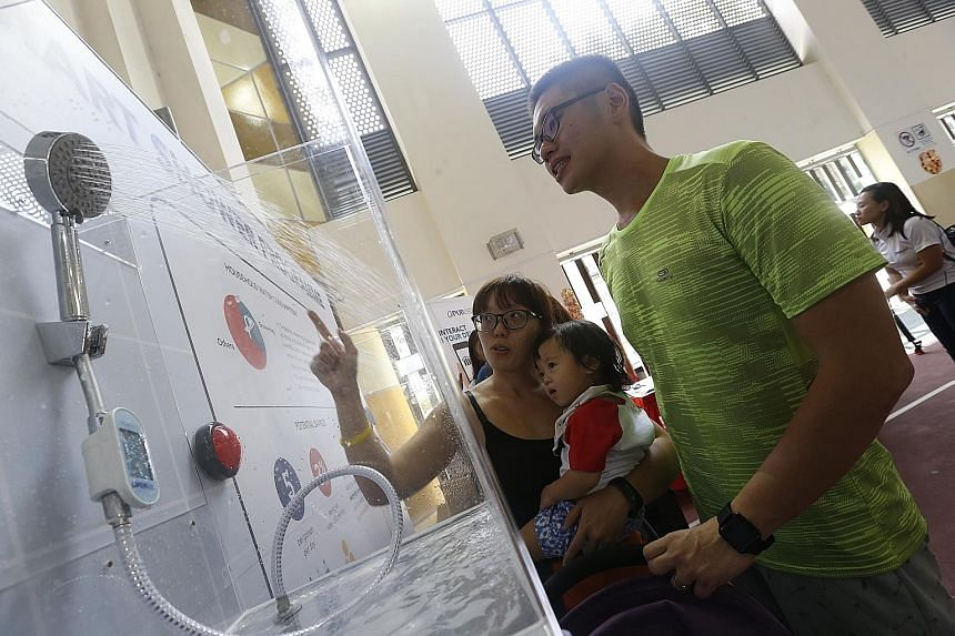 """Army regular Joseph Soh, 30, with his 26-year-old wife Caroline Huang, a housewife, and their child Jaylyn checking out the smart shower device. Ms Huang says the device """"is a very creative solution because it shows me how much I'm using, something I"""