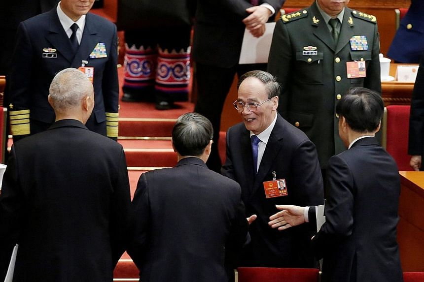 Newly-elected Chinese Vice-President Wang Qishan shaking hands with other officials after the fifth plenary session of the National People's Congress at the Great Hall of the People in Beijing yesterday.
