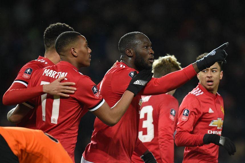 Lukaku (centre) celebrates scoring United's first goal with team mates.