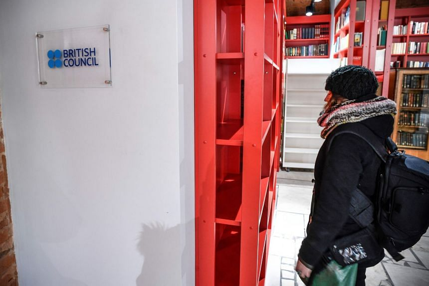 A woman stands next to the entrance of the British Council office in Moscow.